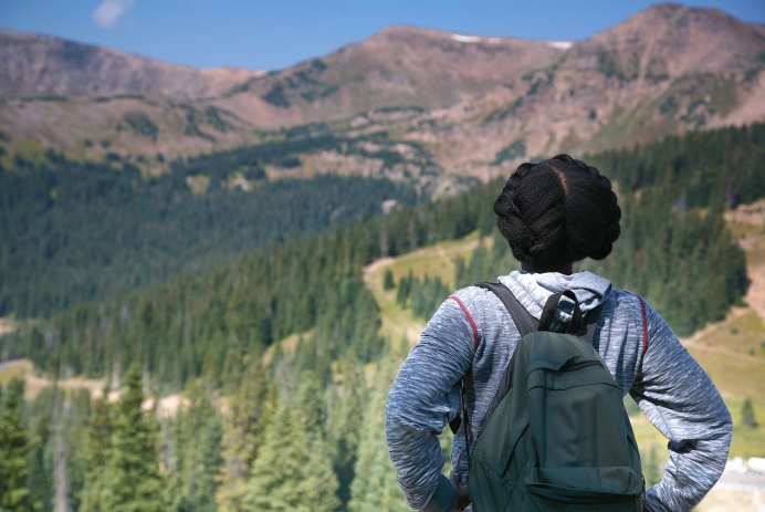 Black teen girl views mid-day landscape of mountains with evergreens and deep blue sky at a national park