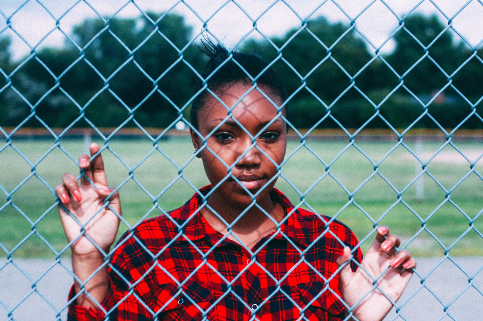 Black teen girl standing against fence, holding on to chain links