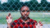 Black girl standing against fence, holding on to chain links