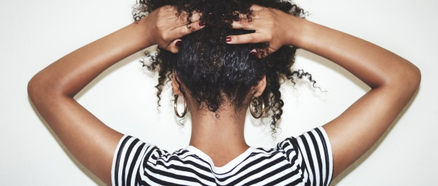 Back of Black girl holding up her curly hair