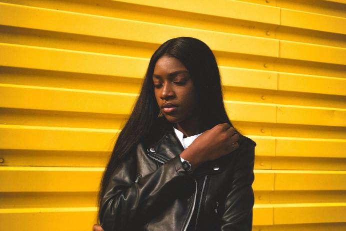 Black girl with long hair standing in front of yellow wall