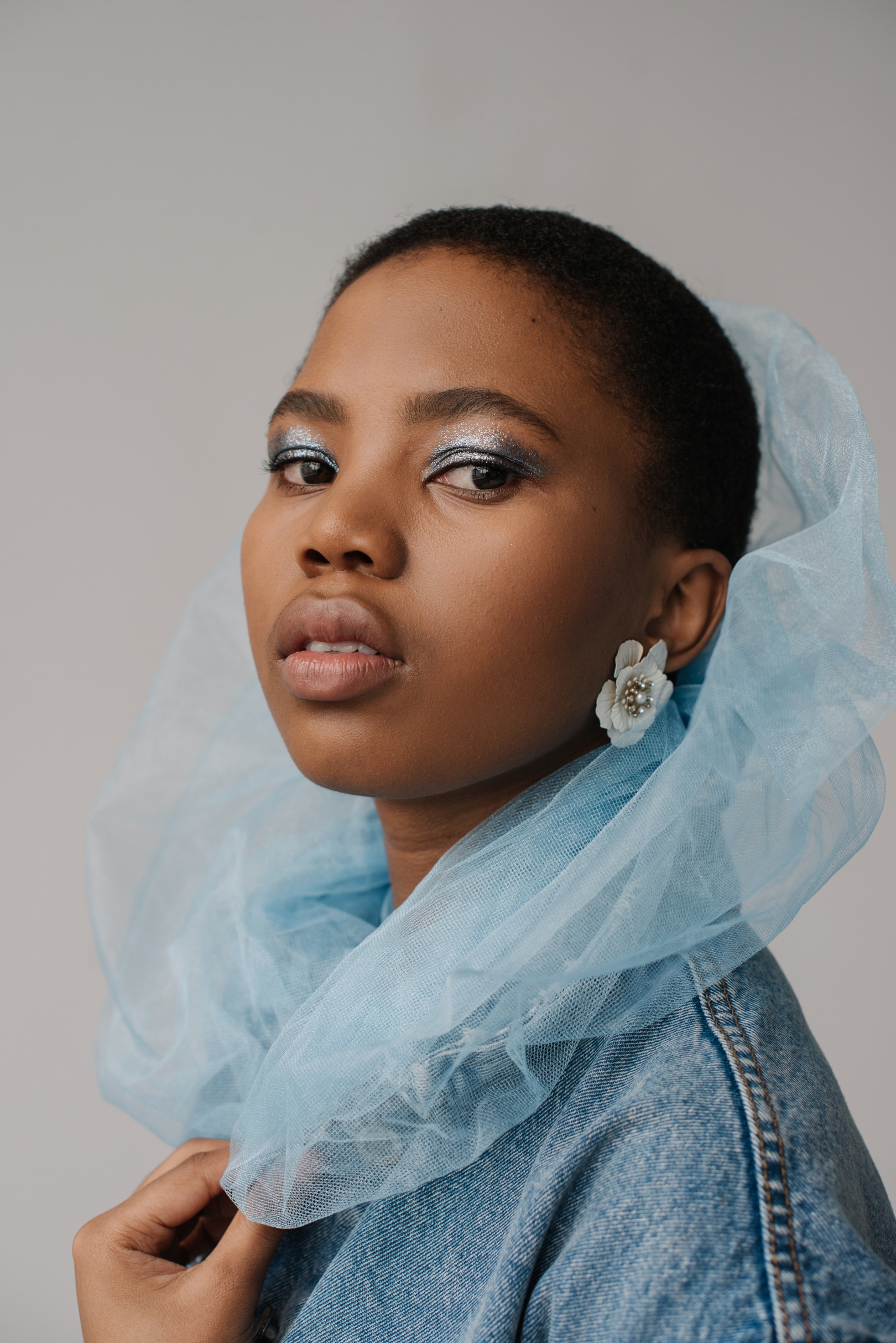 Black girl with blue scarf and denim jacket wearing nude lipstick and blue eye shadow