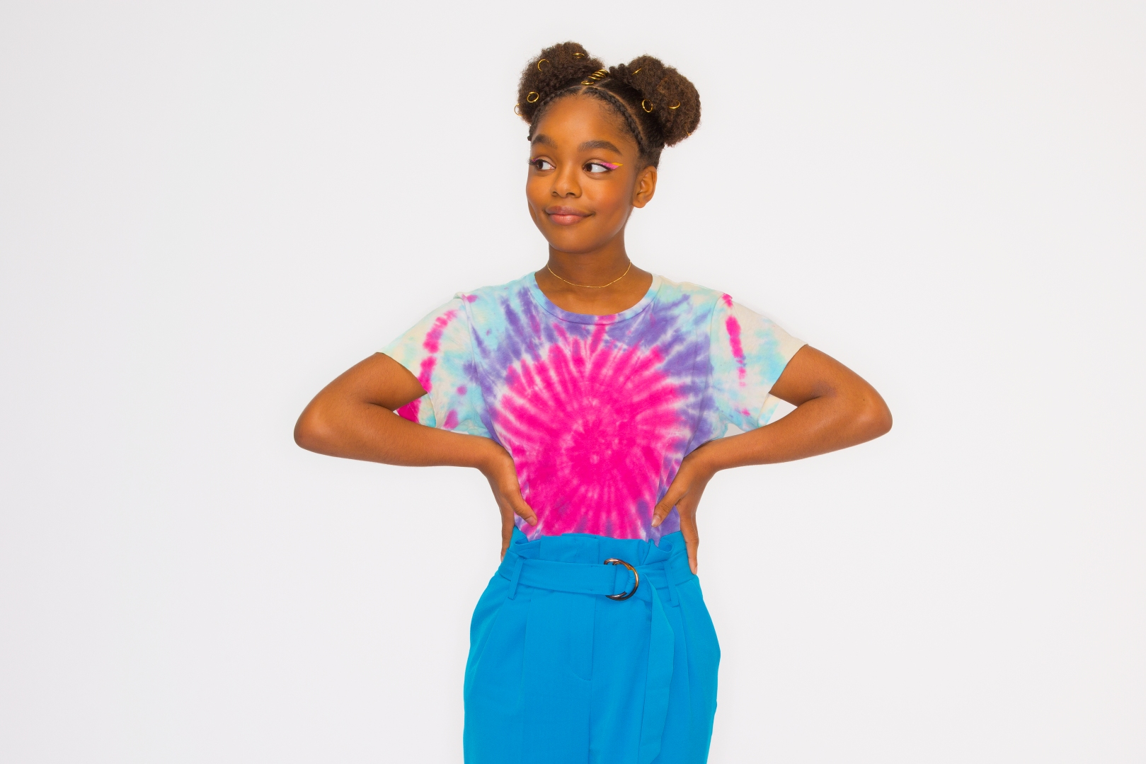 Marsai Martin wearing pink, purple, and blue tie-dyed shirt with blue pants. Her hair is in two side buns.