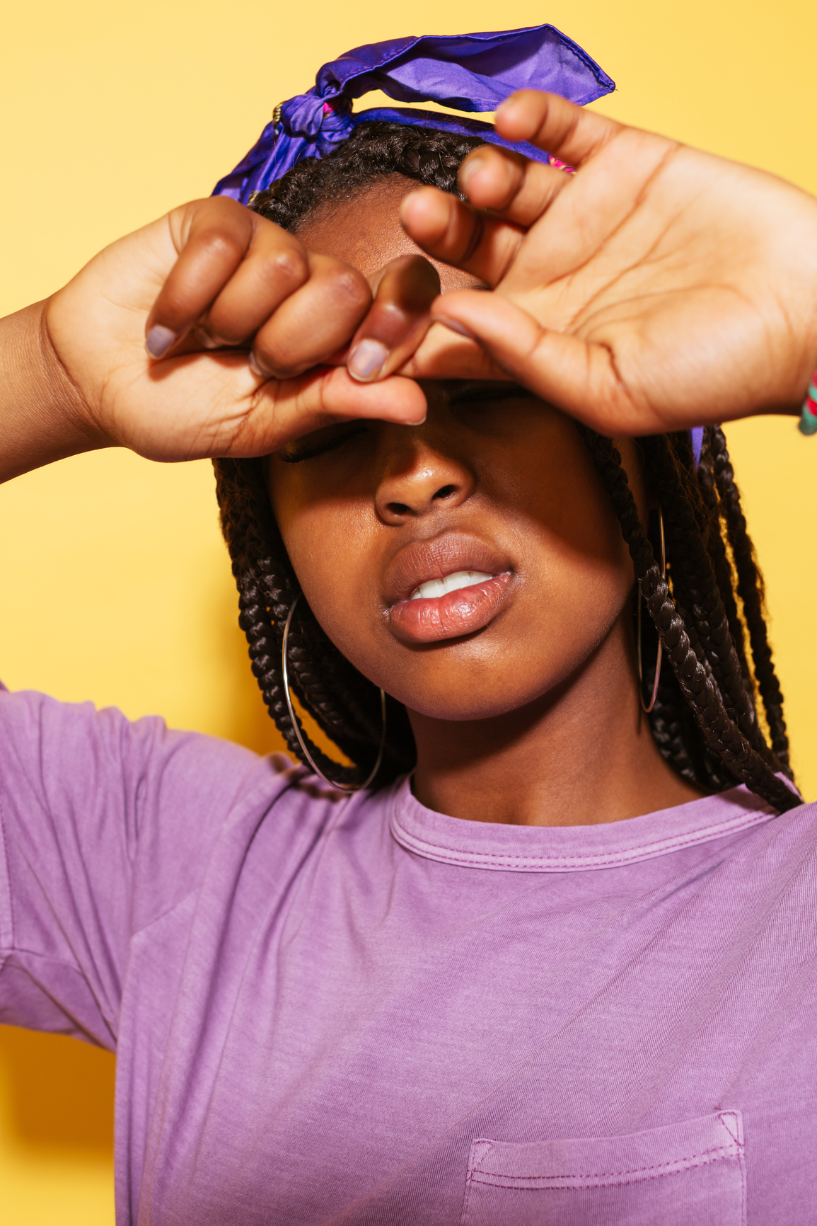Stylish African-American teen girl in violet outfit pulling finger in front of closed eyes against yellow background. Her hair is in braids and she's wearing gold hoop earrings and a purple head scarf.